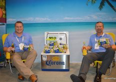 Matt Wentzel and Will Ison with Earth Source Trading enjoy a beer with Corona branded limes at the beach.