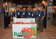 A proud team of Rainier Fruit in front of a customizable bin. Customers can choose the graphics.