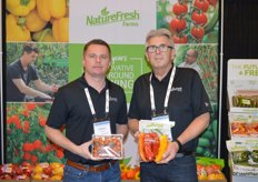 Cornelius Neufeld and Ray Wowryk with NatureFresh Farms show cherry tomatoes on-the-vine and long sweet peppers.