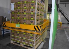 A pallet of kiwis is mechanically being made ready for transport.