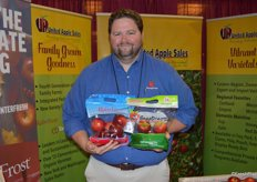 Josh Tunstall with United Apple Sales shows Ruby Frost and SnapDragon apples.