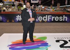 John Toner with United Fresh stands on the new logo of the United Fresh Show at the entrance of the show floor.