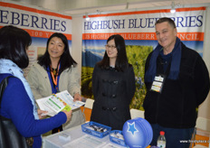 Julia Zhu, Mandy Chen and Thomas Payna are receiving interest from visitors at the stand of the US Highbush Blueberry Council.