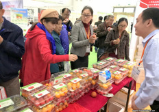Visitors are eagerly trying some tomatoes at the stand of Volpusi, tomato grower and breeder from Shandong Province in China.