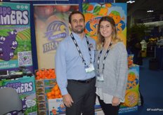 Michael and Erin Reimer with Brandt Farms in front of the Simple Simmons persimmon display.