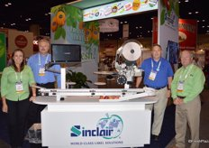 Maria Montalvo, Mark Reed, Chris Faxon and Willard Shay from Sinclair surrounding the POD (Print on Demand) machine. The machine recognizes the fruit or vegetable variety. It prints the PLU and variety/brand on the label.