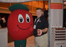 A happy tomato mascot and Michael Prather with Handy Candy, proudly showing the company's tomato cups.