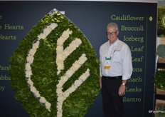Mark McBride with Coastline Family Farms proudly shows the company's logo made out of lettuce and cauliflower.