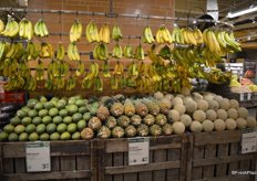 The tropical fruit selection includes bananas, mangos, pineapples and cantaloupes on one side.