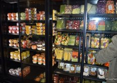 Fresh-cut produce refrigerated and behind glass doors.